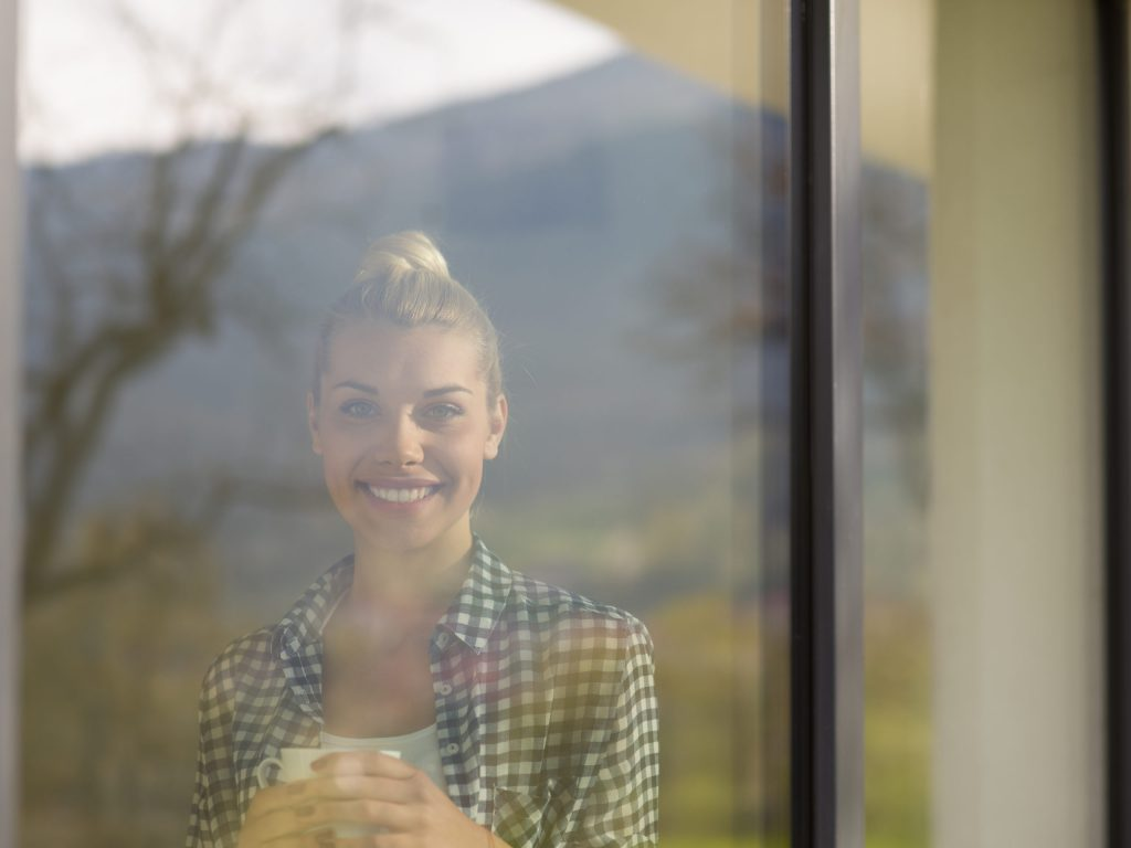 young woman drinking morning coffee by the window to illustrate best home window tinting