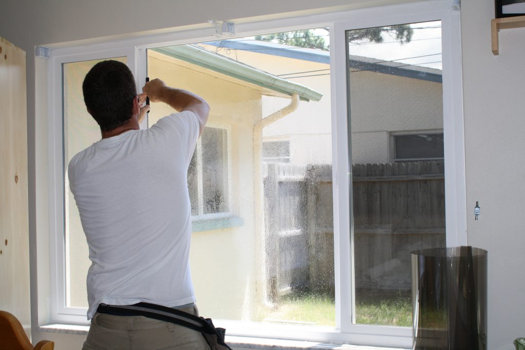 Window tint being applied to a home's windows