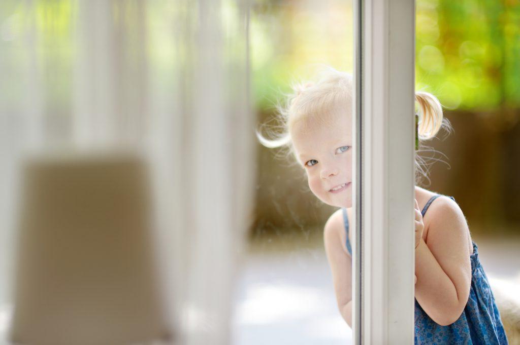 Cute little toddler girl peeking into a window