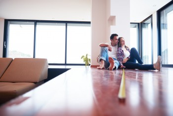 A happy young couple is shown indoors during a home remodeling project.