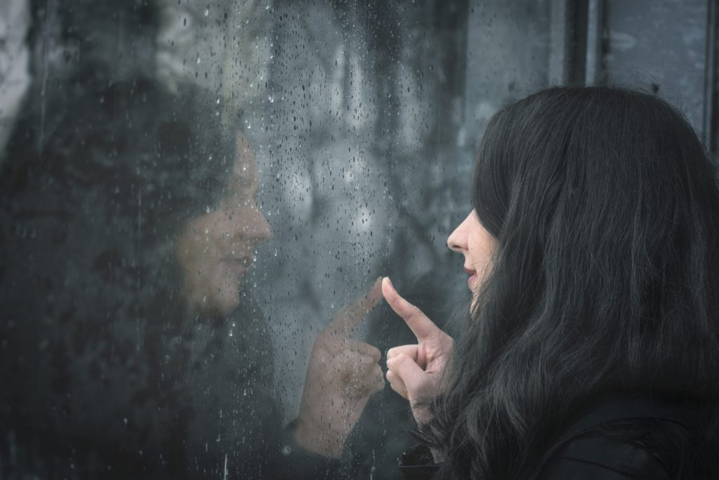 Woman and her reflection on rainy window to illustrate History of Window Tint And Today's Modern Tinting