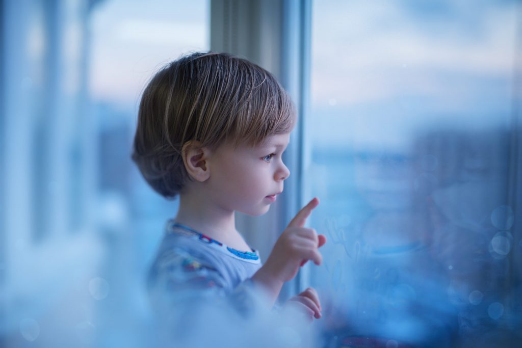 Child looking out window to illustrate window heat loss