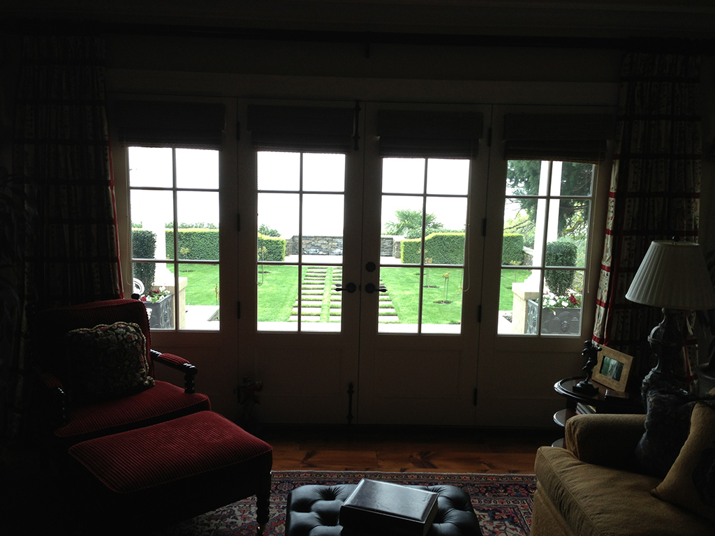 Interior picture looking out closed french doors to nice backyard