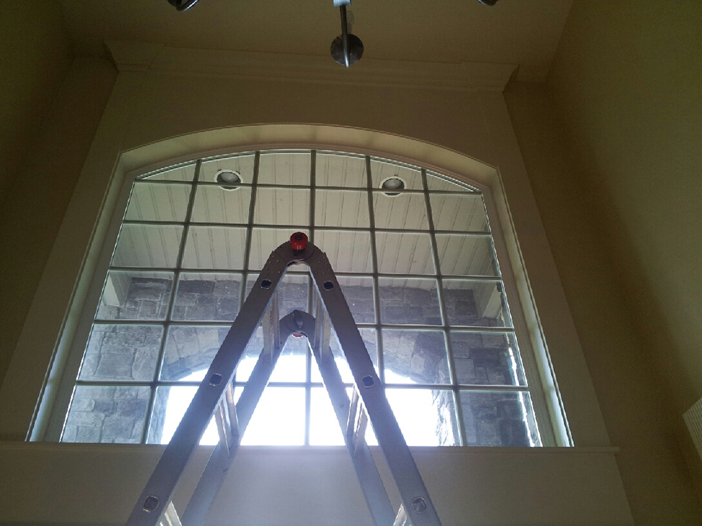 Ladder in front of high entryway windows