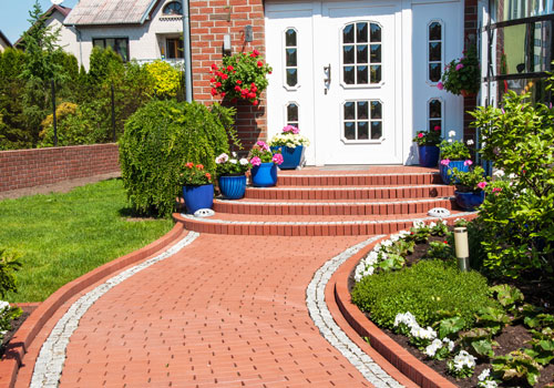 A brick path and neatly trimmed shrubs enhance the front yard of a home with curb appeal.
